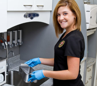 Dental Assistant smiling while cleaning medical tools